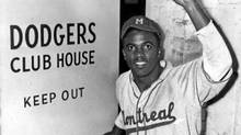 Jackie Robinson, in 1947, wearing his Montreal Royals uniform, steps into the Brooklyn Dodgers clubhouse for the first time. (W.C. Greene/AFP/Getty Images/W.C. Greene/AFP/Getty Images)