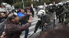 Demonstrators confront riot police during protests against planned reforms by Greece's coalition government in Athens, February 10, 2012. (John Kolesidis/REUTERS/John Kolesidis/REUTERS)