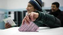 A woman casts her vote in a polling station in Rome February 24, 2013. (STRINGER/REUTERS)