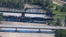 Crews work at the scene of a rail bridge collapse and railcars derailment over the Bow River, southeast of downtown Calgary, Alberta on Thursday, June 27, 2013. (Larry MacDougal/THE CANADIAN PRESS)