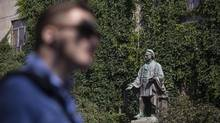 A pedestrian walks past a statue of Egerton Ryerson outside Toronto's Ryerson University on July 6, 2017. (Chris Young/THE CANADIAN PRESS)