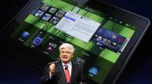 Mike Lazaridis, president and co-chief executive officer of Research In Motion, holds the new Blackberry PlayBook with a screen projection of the device as he speaks at the RIM Blackberry developers conference in San Francisco, California in this September 27, 2010 file photo. (ROBERT GALBRAITH/REUTERS)