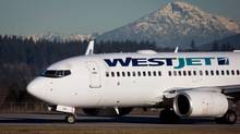 A pilot taxis a Westjet Boeing 737-700 plane to a gate after arriving at Vancouver International Airport in Richmond, B.C., on Monday February 3, 2014. (Darryl Dyck/CP)