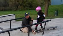 A teenager offers skateboard tips to six-year-old Peyton at a skate park in Cambridge, Ont. (Jeanean Thomas/THE CANADIAN PRESS)