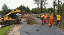In this photo released by the RCMP, workers build a temporary dike to contain water near Slake Lake, Alta. on Saturday July 11, 2011. (THE CANADIAN PRESS)