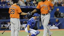 Houston Astros' Chris Carter (23) crosses the plate, greeted by teammate Brett Wallace (29) after hitting a three run homerun during first inning American League action against the Toronto Blue Jays Saturday July 27, 2013 in Toronto. (Jon Blacker/THE CANADIAN PRESS)