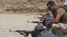 Cpl. Steven Kuzevski, a Canadian Forces MP, trains Afghan National Police officers on the firing range. (DENE MOORE/Dene Moore/The Canadian Press)