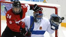 Finland's goalie Noora Raty makes a save while being screened by Canada's Natalie Spooner during their women's ice hockey game at the 2014 Sochi Winter Olympics, February 10, 2014. (Reuters)