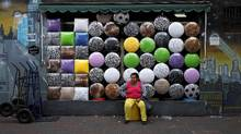 A woman sits in front of a shop selling stools after buying one in the Bras neighborhood of Sao Paulo in this file photo. (NACHO DOCE/REUTERS)