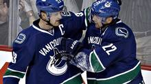 Vancouver Canucks' Henrik Sedin (L) congratulates his brother Daniel after he scored against the Chicago Blackhawks during the second period of their NHL game in Vancouver, British Columbia April 22, 2013. (ANDY CLARK/REUTERS)