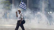 A protester holds a Greek flag as he walks in tear gas outside of the Greek Parliament in central Athens, during a rally against plans for new austerity measures, on Wednesday, June 15, 2011. (Lefteris Pitarakis/Lefteris Pitarakis/AP)