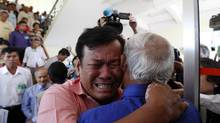 Cambodian former Khmer Rouge servitors, Soum Rithy, left, and Chum Mey, right, embrace each other after the verdicts were announced, at the U.N.-backed war crimes tribunal in Phnom Penh, Cambodia, Thursday, Aug. 7, 2014. (Heng Sinith/AP)