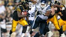 Chevon Walker of the Hamilton Tiger-Cats avoids a tackle by Toronto Argonauts' Armond Armstead during Canadian Football League action at Ivor Wynne Stadium in Hamilton, Ontario, Saturday, July 14, 2012. (Geoff Robins/THE CANADIAN PRESS)