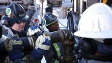 Workers assemble high-pressure pipe at hydraulic fracturing operation near Bowden, Alta., in February 2012. B.C. is planning to ramp up its own fracking activities. (Jeff McIntosh for The Globe and Mail)