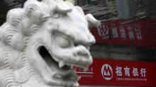 A Chinese stone lion sits beside a branch of China Merchants Bank in Shanghai. (ALY SONG)