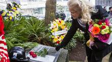 Carol Davis, widow of construction worker Donald Davis, places a rose on a memorial in Vancouver on Wednesday during a ceremony marking the 35th anniversary of the Bentall tragedy, in which four construction workers plunged to their deaths. (Ben Nelms For The Globe and Mail)