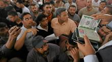 A Hamas policeman looks at the passports of Palestinians waiting to cross into Egypt at the Rafah border crossing in the southern Gaza Strip June 1, 2010. (Mohammed Salem/Reuters)