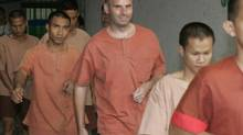 Former teacher Christopher Neil, centre, walks with other prisoners to a prison bus after a court appearance in Bangkok, Thailand, in January 2008. (APICHART WEERAWONG/The Associated Press)