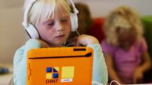 A girl listens to music on her iPad at the Steve Jobs school in Sneek Aug. 21, 2013. The Steve Jobs schools in the Netherlands are founded by the O4NT (Education For A New Time) organization, which provides the children with iPads to help them learn with a more interactive experience. (� Michael Kooren / Reuters/REUTERS)