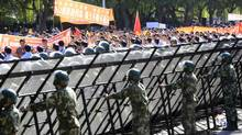 Paramilitary police officers hold railings as demonstrators protest outside the Japanese Embassy in Beijing, China, on Tuesday, Sept. 18, 2012. (Nelson Ching/Bloomberg)