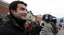 Rick Mercer watches the torch go by in Rossland, British Columbia, Canada while taping segments for the Rick Mercer Report during the town's winter carnival, which was moved to coincide with the arrival of the Vancouver 2010 Olympic Torch Relay. (Deborah Baic/The Globe and Mail/Deborah Baic/The Globe and Mail)