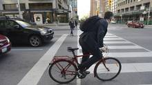 A cyclist pedals away on the green light at the intersection at Bay St.and Bloor St. West on June 3 2013. (2013 file photo) (Fred Lum/The Globe and Mail)