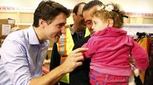 Prime Minister Justin Trudeau greets Syrian refugees at Toronto Pearson International Airport, Dec. 11, 2015. (MARK BLINCH/REUTERS)
