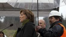 Construction worker Howard Bassett holds an umbrella over B.C. Premier Christy Clark during her announcement of the 50 per-cent completion of the South Fraser perimeter road in Surrey, British Columbia, April 3, 2012. (Ben Nelms For The Globe and Mail/Ben Nelms For The Globe and Mail)