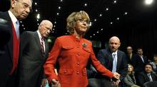Former U.S. Rep. Gabrielle Giffords is assisted by her husband, retired U.S Navy Captain Mark Kelly, right, prior to a Senate Judiciary Committee hearing on gun violence, on Capitol Hill in Washington, Jan. 30, 2013. The hearing comes six weeks after the massacre of 26 people at a Connecticut school ignited new calls to fight gun-related violence. (LARRY DOWNING/REUTERS)