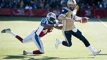 Winnipeg Blue Bombers' quarterback Joey Elliott (14) breaks away from Montreal Alouettes' Kenny Ingram (43) during second half CFL football action in Montreal, Monday, October 8, 2012. (Graham Hughes/THE CANADIAN PRESS)