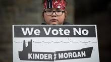 Jamie Antone, 9, of the Squamish First Nation, holds a sign as protesters gather outside National Energy Board hearings on the proposed Trans Mountain pipeline expansion in Burnaby, B.C., on Tuesday January 19, 2016. The proposed $5-billion expansion would nearly triple the capacity of the pipeline that carries crude oil from near Edmonton to the Vancouver area to be loaded on tankers and shipped overseas. (DARRYL DYCK/THE CANADIAN PRESS)