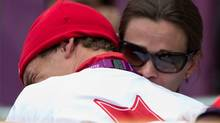 Simon Whitfield is hugged by his wife after crashing in the men's triathlon at Hyde Park during the Summer Olympics in London on Tuesday, August 7, 2012. (The Canadian Press)