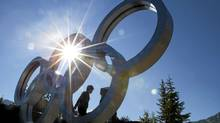 Tourists in Whistler, B.C. September 2, 2011 climb on the Olympic rings by Olympic Plaza which will be hosting the Whistler Jazz Festival this weekend. (John Lehmann/The Globe and Mail/John Lehmann/The Globe and Mail)