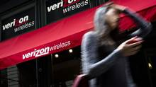 A pedestrian uses her cellphone as she passes a Verizon Wireless store on Broadway in Lower Manhattan. (John Minchillo/AP)
