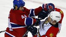 Montreal Canadiens defenseman Roman Hamrlik (L) hits Florida Panthers left wing David Booth during the second period of their NHL hockey game in Montreal February 2, 2011. REUTERS/Shaun Best (SHAUN BEST)