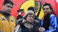 Attawapiskat Chief Theresa Spence holds hands with fellow hunger striker Jean Socks as she stands beside supporter Danny Metatawabin during a press conference outside her teepee on Victoria Island in Ottawa on Friday, Jan. 4, 2013. (Sean Kilpatrick/THE CANADIAN PRESS)