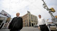 Allied Property's Michael Emory, left, and architect Dermot Sweeny outside of the Queen Richmond Centre West project. The plan is to build an 11-story structure over the top of the century-old five-storey industrial building, seen behind. (Fred Lum/Fred Lum/The Globe and Mail)