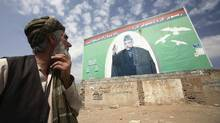 An Afghan man looks at an election billboard of Afghan President Hamid Karzai Monday. Major fraud complaints in the Afghan presidential election have surged to nearly 700, raising concern that the volume of cases that must be investigated will delay announcement of a winner and formation of a new government. (Musadeq Sadeq)