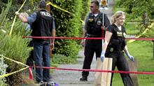 Seattle Police Department crime scene investigators collect evidence from a crime scene in a West Seattle neighborhood where a gunman shot himself after being confronted by police in Seattle, Washington May 30, 2012. The gun the gunman used to shoot himself is at the lower left of photo near the yellow number 1 and number 2 markers. Earlier in the day the gunman shot two men and a woman to death at a popular Seattle cafe, then fled to a downtown parking lot, where he fatally shot another woman and stole her car. (Marcus Donner/Reuters/Marcus Donner/Reuters)