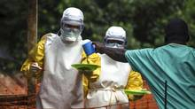 Medical staff working with Medecins sans Frontieres (MSF) prepare to bring food to patients kept in an isolation area at the MSF Ebola treatment centre in Kailahun July 20, 2014. (STRINGER/REUTERS)