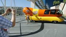 """Tourists snap photographs with a Oscar Mayer Wienermobile in the background at an official Oscar Mayer """"Sing the Jingle, Be a Star"""" event in Las Vegas May 23, 2006. (JAE C. HONG/AP)"""