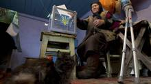 A local resident casts her vote during the parliamentary elections inside a house in the village of Orane, some 100 km northwest of Kiev October 28, 2012. (Konstantin Pahomov/REUTERS)