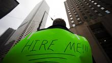 A man, with a sign strapped to his back, uses a megaphone to attract the attention of potential employers as he hands out resumes on Bay Street in the financial district in Toronto, March 5, 2009. (Mark Blinch/REUTERS)