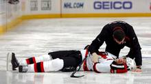 Head trainer Richard Stinziano of the New Jersey Devils goes to the aid of Patrik Elias of the Devils who lies motionless on the ice after being checked by Ryan Wilson of the Colorado Avalanche during NHL action at the Pepsi Center on January 16, 2010 in Denver, Colorado. (David Zalubowski/David Zalubowski/AP)