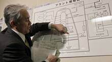 A Tokyo Electric Power official points at an illustration of a nuclear plant as he answers reporters' questions at the disaster centre in Fukushima, northern Japan on March 15, 2011. (YURIKO NAKAO/Yuriko Nakao/Reuters)