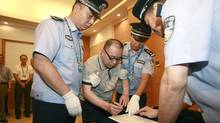 Alleged smuggling kingpin Lai Changxing (C) is escorted by policemen as he signs a warrant issued for his arrest at the Beijing Capital International Airport in Beijing, July 23, 2011 in this photo distributed by China's official Xinhua News Agency. Lai was repatriated back to China on Saturday afternoon 12 years after fleeing to Canada, according to the Ministry of Public Security. (XINHUA/REUTERS)