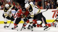 Chicago Blackhawks centre Marcus Kruger (16) and Boston Bruins left wing Milan Lucic (17) battle for the control of the puck during the third period of Game 1 in their NHL Stanley Cup Final series, Wednesday, June 12, 2013, in Chicago. (Nam Y. Huh/AP)