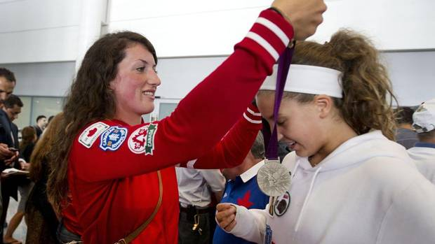 Olympic medalist Natalie Mastracci (women's eight rowing) hangs her silver medal on 14-year-old Silvia Stajer after arriving at Toronto's Pearson Airport, Aug. 13, 2012. Stajer asked Mastracci for an autograph and got to wear her medal as well. (Moe Doiron/The Globe and Mail)