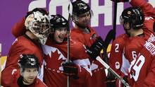 Teammates gather around Canada goaltender Carey Price as they celebrate their 1-0 victory in the men's hockey semi-final at the Sochi Winter Olympics Friday, February 21, 2014 in Sochi. (CP)