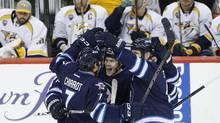 WinnipegJets' Ben Chiarot (7), Nikolaj Ehlers (27) and Mark Stuart (5) celebrate Ehlers' goal against the Nashville Predators during third period NHL action in Winnipeg on Thursday, January 14, 2016. (John Woods/THE CANADIAN PRESS)